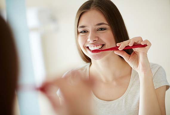 woman brushing her teeth that were recently cleaned by a dental hygienist