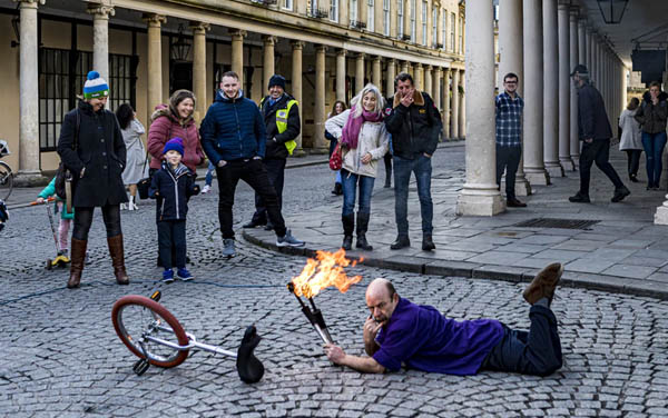 man on ground next to his unicycle holding fire