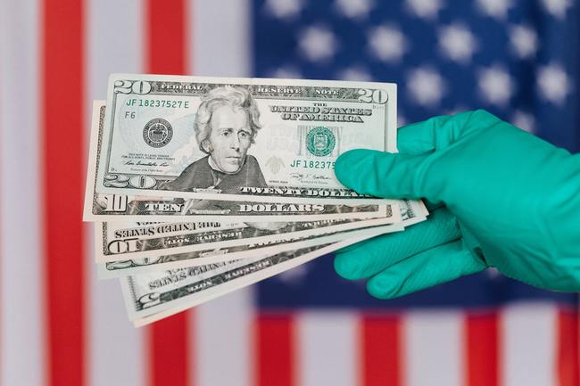 surgical gloved hand holding united states currency